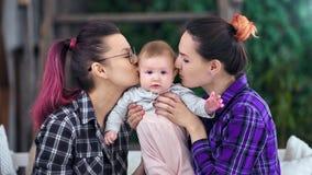 摆在逗人喜爱的矮小的婴孩看照相机在两亲吻和拥抱他的愉快的母亲期间 影视素材