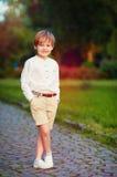 摆在逗人喜爱的年轻时兴的男孩画象户外 图库摄影