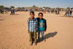 摆在通过荒废村庄的人群的两个男孩 免版税库存图片