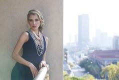 摆在都市阳台的美丽的妇女有城市视图 库存图片