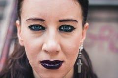 摆在都市风景的一个俏丽的goth女孩的特写镜头 免版税库存图片