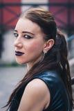 摆在都市风景的一个俏丽的goth女孩的特写镜头 免版税库存照片