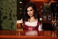 摆在酒吧柜台的美丽的性感的妇女侍酒者 图库摄影