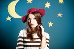 摆在酒红色的帽子的沉思深色的夫人  免版税图库摄影