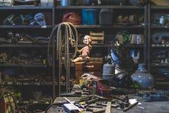 摆在金属商店里面的肮脏的塑料娃娃 免版税库存照片