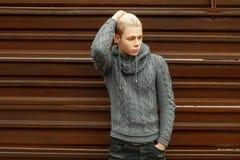 摆在金属墙壁附近的被编织的毛线衣的英俊的年轻人 免版税库存照片