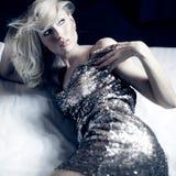 摆在金礼服的有吸引力的白肤金发的秀丽 图库摄影