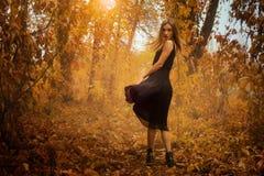 摆在金黄秋天木头的照相机的黑礼服的美丽的女孩 库存照片