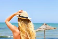 摆在金黄比基尼泳装的性感的白肤金发的时髦的女人 库存照片