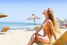 摆在金黄比基尼泳装的性感的年轻白肤金发的时髦的女人 免版税库存图片