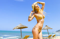 摆在金黄比基尼泳装的白肤金发的时髦的女人 免版税库存图片