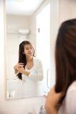 摆在镜子前面的亚裔妇女,愉快地微笑 免版税库存照片