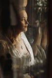 摆在镜子,性感的wom的反射附近的华美的白肤金发的新娘 库存图片