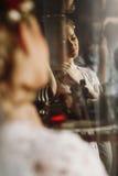 摆在镜子,性感的wom的反射附近的华美的白肤金发的新娘 图库摄影
