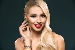 摆在镯子和耳环的可爱的白肤金发的妇女画象, 库存照片