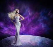 摆在长的礼服,妇女头发挥动的风的时装模特儿 免版税库存照片