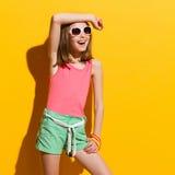 摆在阳光下的微笑的女孩 免版税库存照片