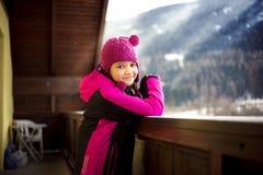 摆在阳台的逗人喜爱的微笑的女孩反对多雪的阿尔卑斯 库存照片