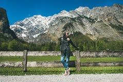 摆在阿尔卑斯前面山景的女性旅行家  免版税图库摄影