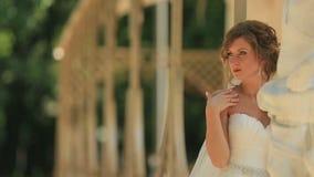 摆在雕象附近的美丽的肉欲的白肤金发的新娘在遮荫庭院里 股票视频