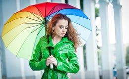 摆在雨中的鲜绿色的外套的美丽的妇女拿着一把多彩多姿的伞 免版税图库摄影