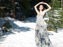 摆在雪妇女的通风美丽的礼服 免版税库存图片
