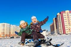 摆在雪滑行车的双胞胎 免版税库存图片