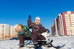 摆在雪滑行车的双胞胎 免版税图库摄影