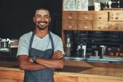 摆在靠近柜台的年轻微笑的barista在他的咖啡馆 免版税库存图片