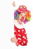 摆在面板之后的一个微笑的男性小丑 库存照片