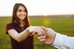 摆在领域的背景中的一个女孩,看另外一半和给人他的手、广告和insertin 免版税库存照片