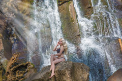 摆在飞溅水和明亮的太阳的瀑布的背景的美丽的皮包骨头的女孩 免版税库存照片