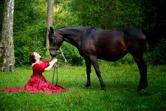 摆在马附近的减速火箭的礼服的美丽的女孩 库存图片