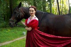 摆在马附近的减速火箭的礼服的美丽的女孩 免版税库存图片