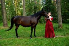 摆在马附近的减速火箭的礼服的美丽的女孩 免版税库存照片