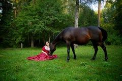 摆在马附近的减速火箭的礼服的美丽的女孩 库存照片