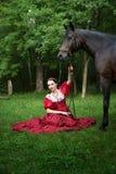 摆在马附近的减速火箭的礼服的美丽的女孩 图库摄影