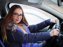 摆在驾驶席的玻璃的年轻白肤金发的妇女在汽车手上在方向盘 外面雪飞雪和雨 免版税库存照片