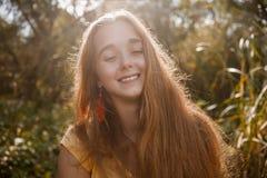摆在高草前面的愉快的女孩在有她的眼睛的一个公园结束了减速火箭的颜色 图库摄影
