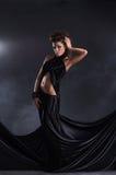 摆在黑色礼服的性感的妇女 免版税库存图片