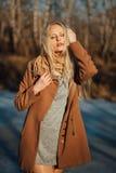 摆在以春天自然为背景的外套的美丽的女孩 免版税库存照片