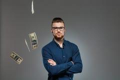摆在黑暗的背景的落的金钱中的年轻成功的商人 库存图片