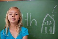 摆在黑板前面的白肤金发的女小学生 免版税库存图片