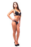 摆在黑比基尼泳装的性感的少妇隔绝在白色背景 免版税库存照片