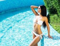 摆在水池旁边的泳装的诱人的少妇 库存照片
