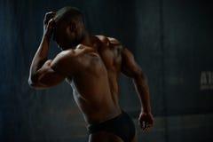 摆在黑演播室背景的性感的英俊的非裔美国人的男性身体建造者 人的秀丽和完美 免版税库存图片