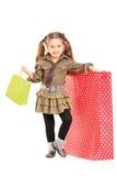 摆在购物袋旁边的女孩的全长纵向 免版税库存图片