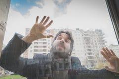 摆在玻璃后的年轻英俊的有胡子的人 免版税图库摄影