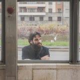 摆在玻璃后的年轻英俊的有胡子的人 库存图片