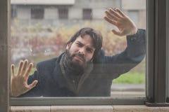 摆在玻璃后的年轻英俊的有胡子的人 免版税库存照片